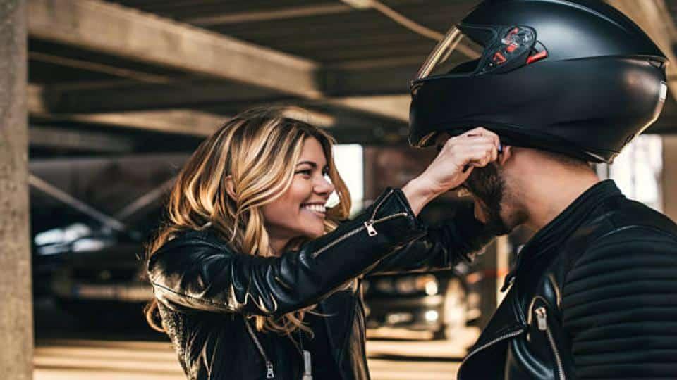 woman puts helmet on a man's head