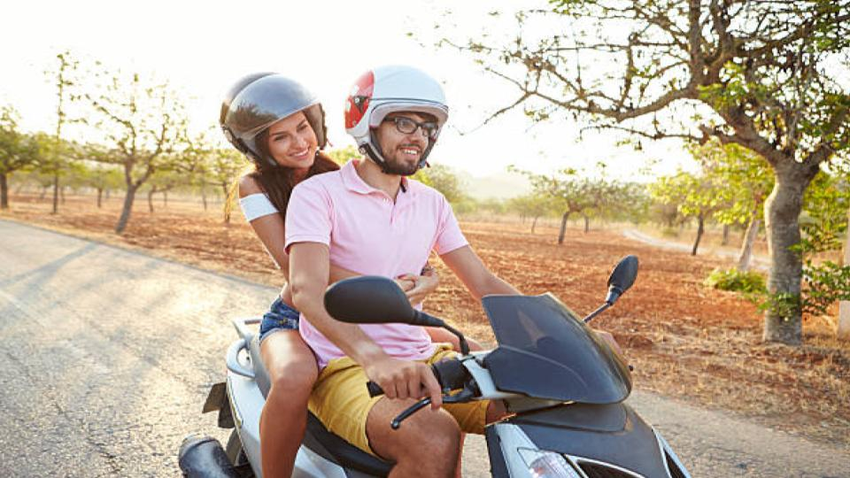 man and woman riding a scooter