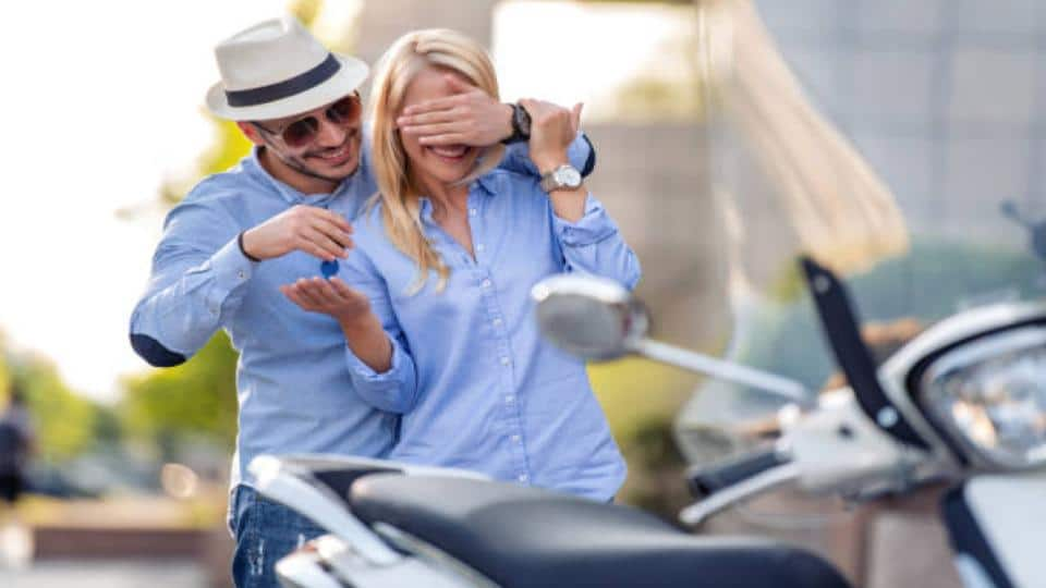 man handing a motorcycle key to a woman
