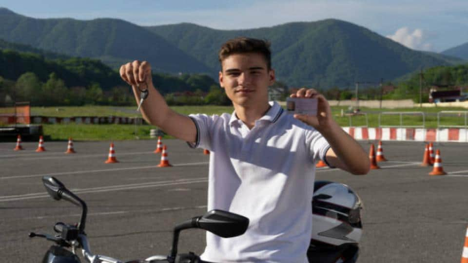 teen holding a driver's license and motorcycle key